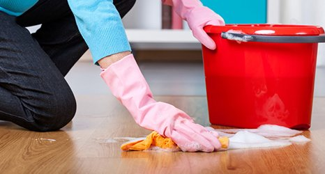 Girl on hand and knees cleaning floor with red bucket