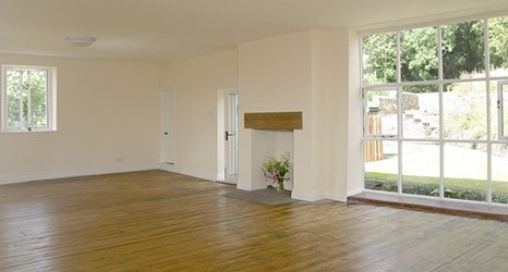 Empty house with cream walls and fireplace with no fire